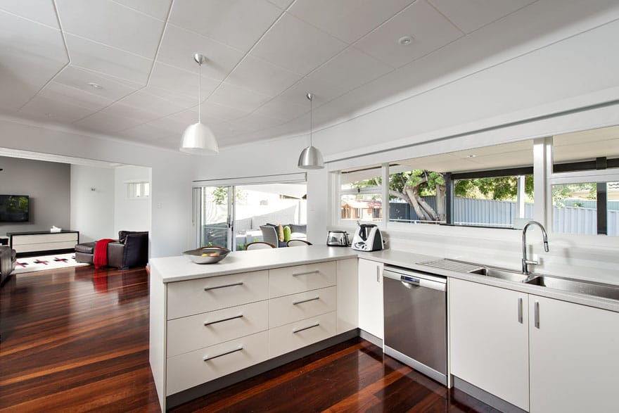 The strategic choice of lighting over the kitchen bench makes it more practical for food preparation.